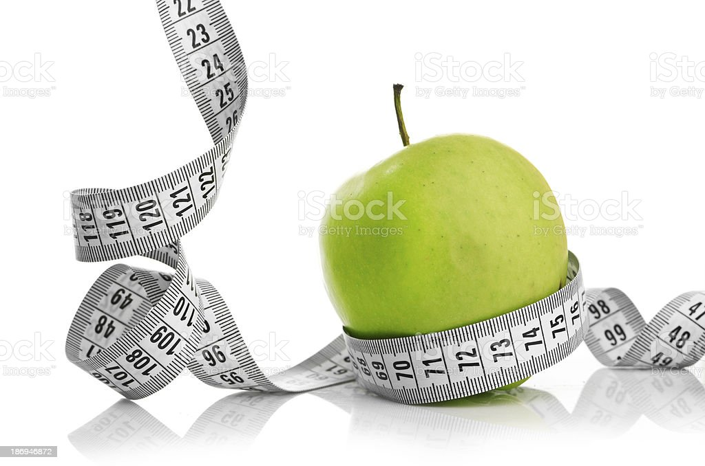 Measuring tape wrapped around a green apple royalty-free stock photo