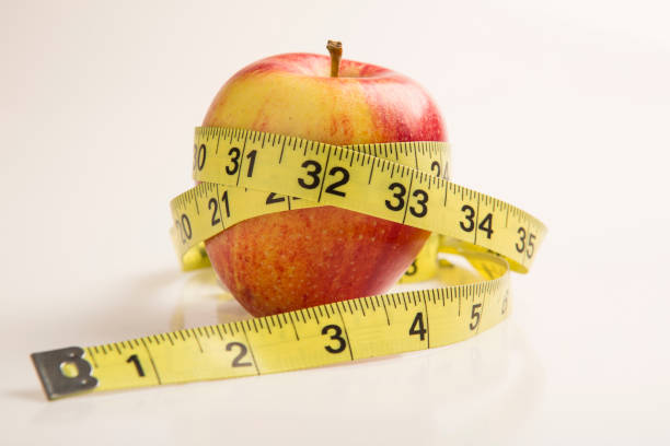 Measuring tape wrapped around a red apple. Diet concept stock photo