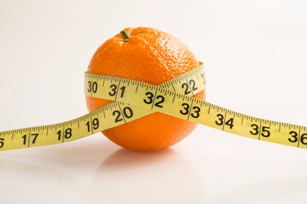 Measuring tape wrapped around an Orange. Diet concept stock photo