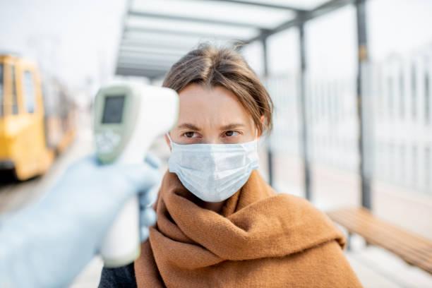 Het meten van temperatuur van een jonge vrouw in gezichtsmasker bij een controlepost in openlucht foto