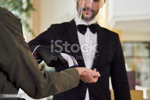 Young man wearing rubber gloves and face shield while putting an infrared thermometer to the wrist of woman
