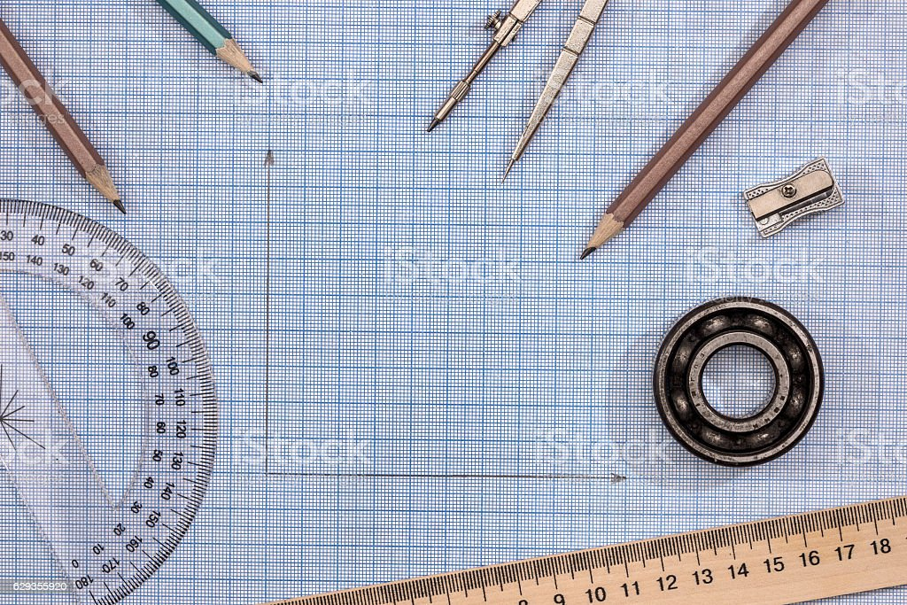 Measuring tools above  blue graph paper. stock photo