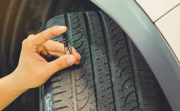 meten slijtage van het loopvlak van een band op een auto. veilig te gebruiken op een dagelijkse basis. - tyre stockfoto's en -beelden
