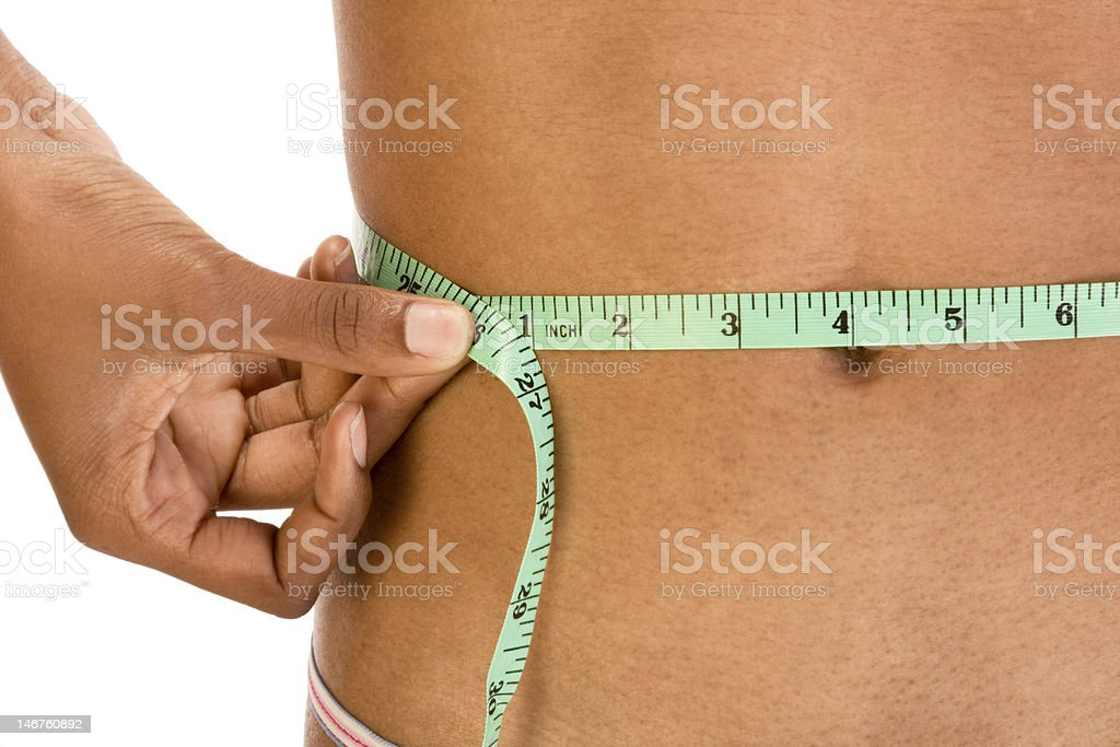 Measuring waist, close up of ethnic woman abdomen royalty-free stock photo