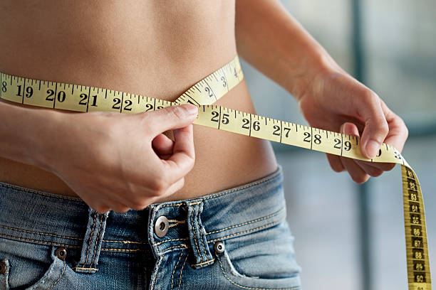 measuring waist close up - slim stock pictures, royalty-free photos & images