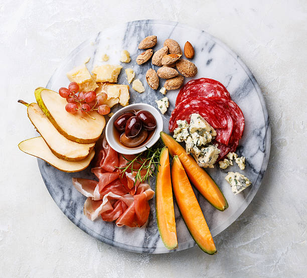 meat and cheese plate with ham, cheese, melon and olives - melonenbirne stock-fotos und bilder