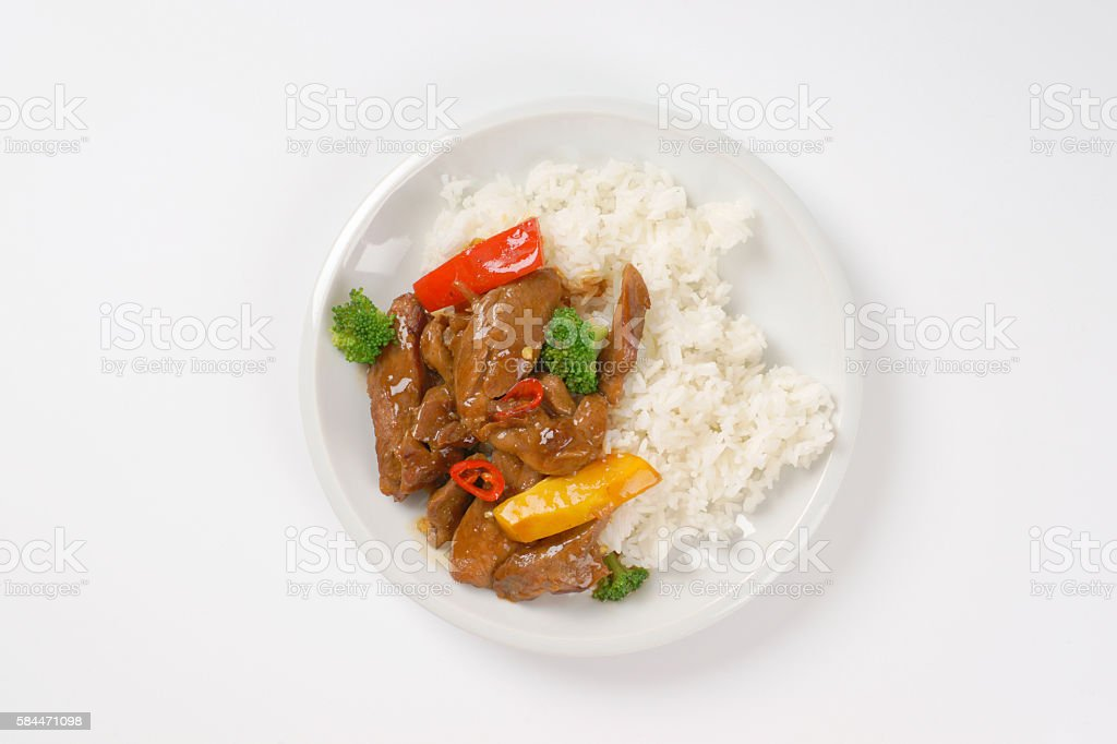 meat and vegetable stir fry with rice stock photo