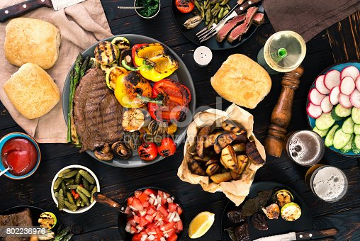 685404620istockphoto Meat and vegetables cooked on a grill on a dark wooden table with wine and beer 802236976