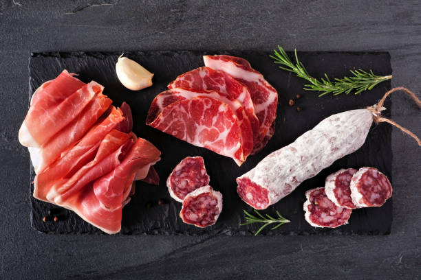 Meat appetizer platter with sausage, and cold cuts, above view on a slate serving board stock photo