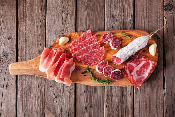 Meat appetizer platter with sausage, prosciutto, ham and salami, top view on a serving board against wood stock photo