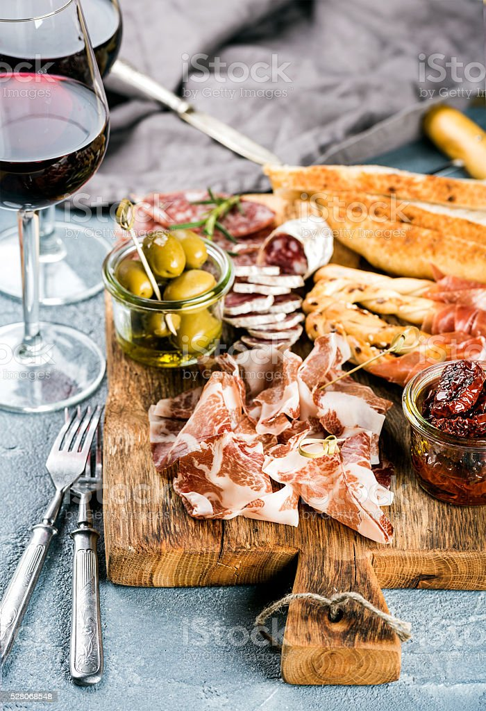 Meat appetizer selection. Salami, prosciutto, bread sticks, baguette, olives and stock photo