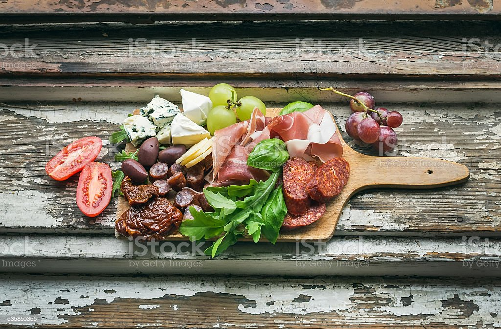 Meat appetizers selection on the old painted wood background stock photo