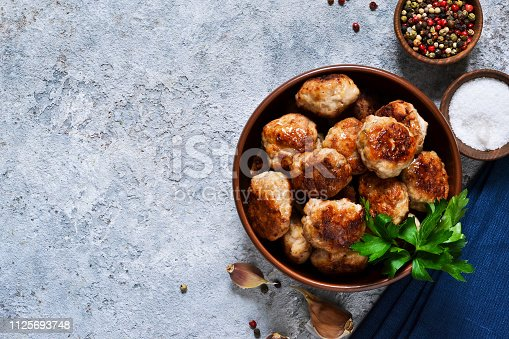 Meat balls with spices on a concrete background. View from above.