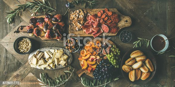istock Meat, cheese, olives, sandwiches, prosciutto, buns on wooden background 872631772