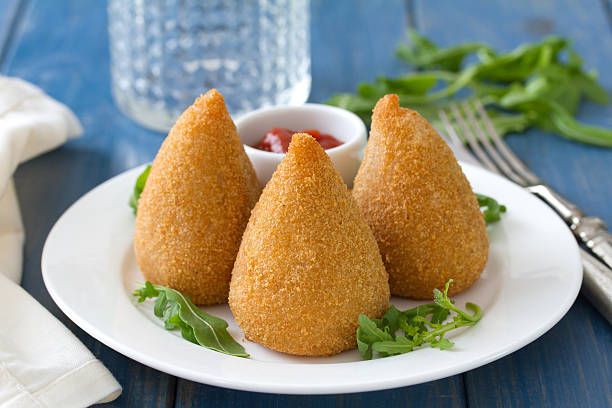 meat croquette on white plate on blue wooden background - coxinha stock photos and pictures