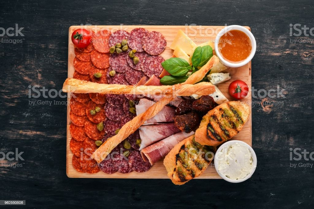 Meat cut and cold snacks. Italian cuisine. On a wooden background. Top view. Copy space. - Royalty-free Antipasto Stock Photo