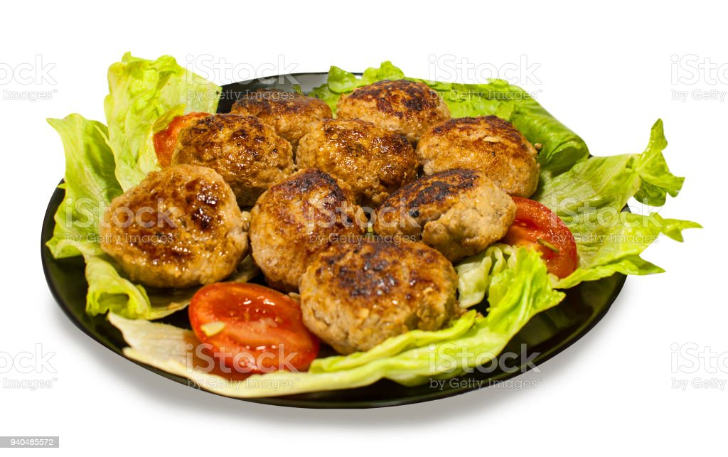 Meat cutlets on lettuce leaves with slices of tomatoes. The view from the top. stock photo