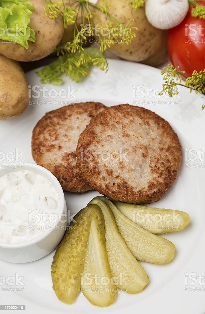 meat cutlets with sauce and garnish on white plate royalty-free stock photo