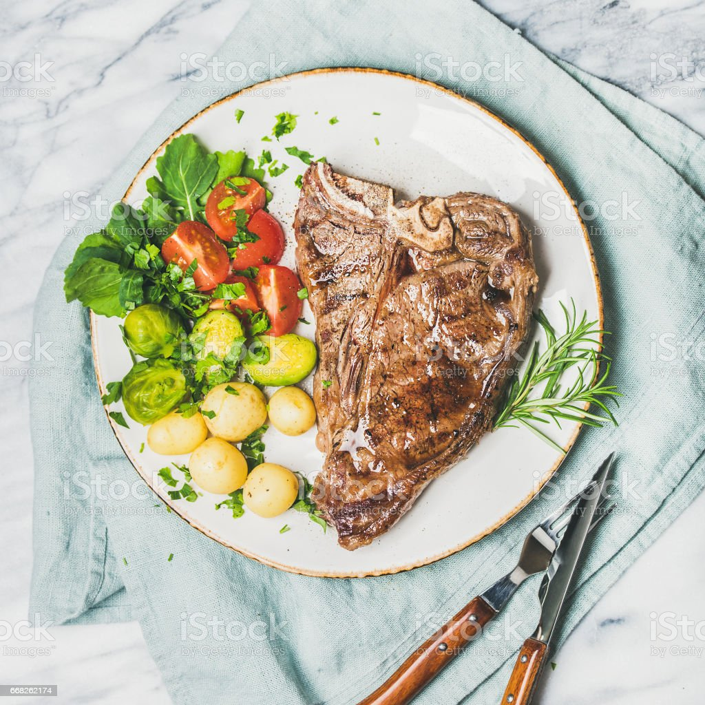 Meat dinner plate with cooked beef tbone steak, square crop foto stock royalty-free