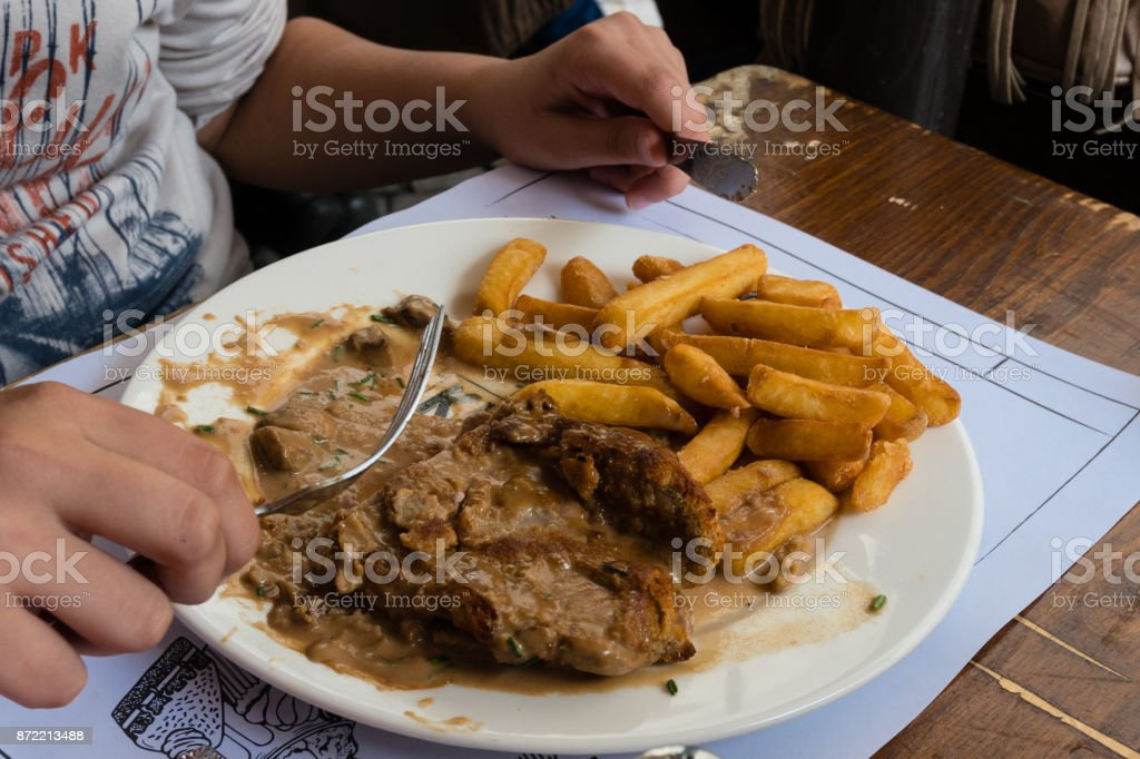meat dish with potatoes on the table in a bistro in Strasbourg stock photo