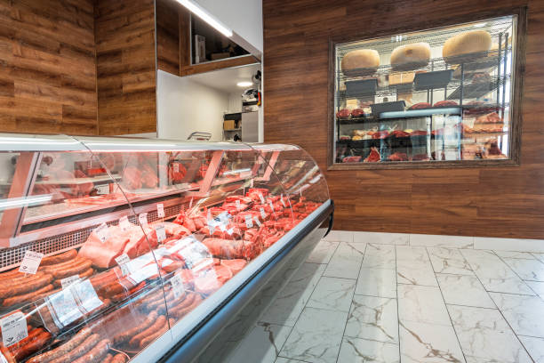 meat display refrigerator and walk in refrigerator in a grocery store - delis stock photos and pictures