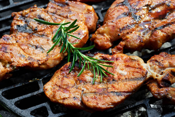 Meat during grilling. Chuck steak with herbs and spices stock photo