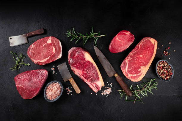 Meat flat lay. Various cuts of meat, overhead flat lay shot with knives, salt, pepper, and herbs stock photo