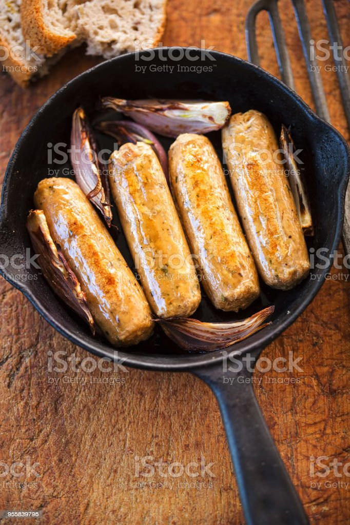 Meat free (quorn) mycoprotein sausages with red onions on skillet stock photo