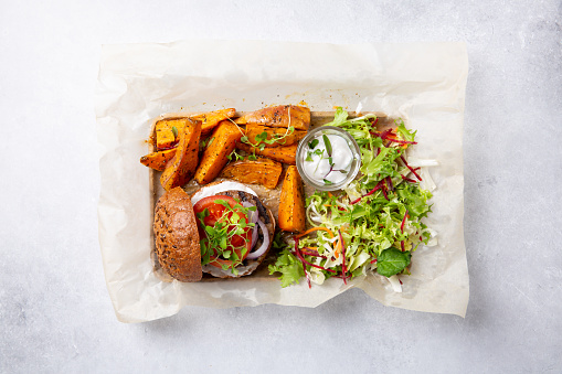 Meat free plant based burger served with sweet potato wedges, green mix salad and white sauce on gray table. Healthy vegan or vegetarian food concept. Top view.