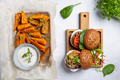 Meat free plant based burgers served with sweet potato wedges, green mix salad and white sauce on gray table. Healthy vegan or vegetarian food concept. Top view.