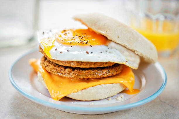 Meat free sausage flavour patties with cheese and egg on breakfast muffin stock photo