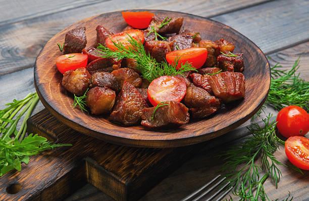 meat fried small pieces of roast goulash - schweinegulasch stock-fotos und bilder