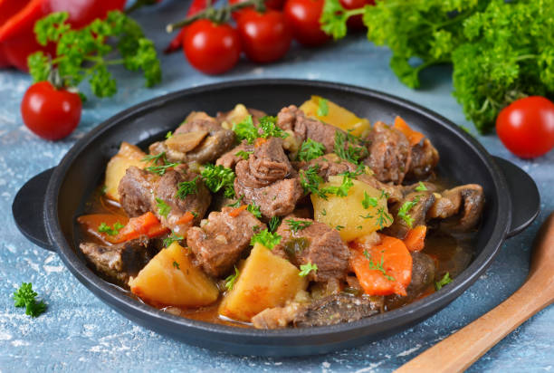 Meat goulash with vegetables, potatoes and mushrooms on concrete, grunge background stock photo