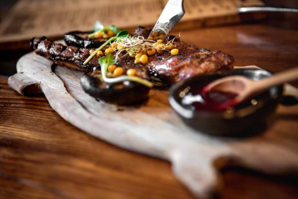 fleisch in einer pfanne mit gemüse und sauce - steak anbraten stock-fotos und bilder