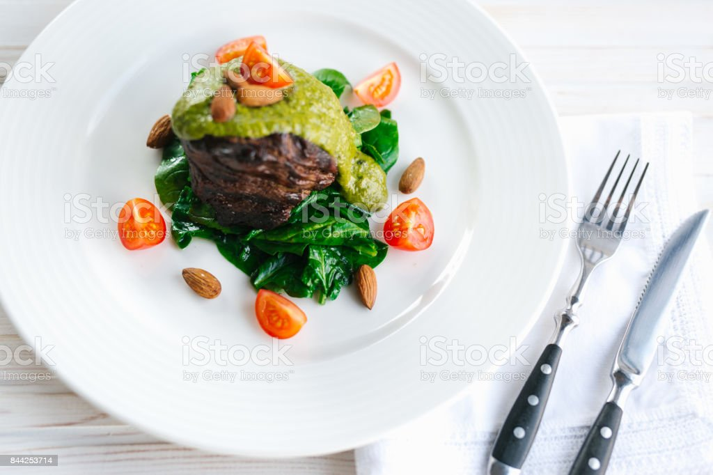 meat in a spinach sause stock photo