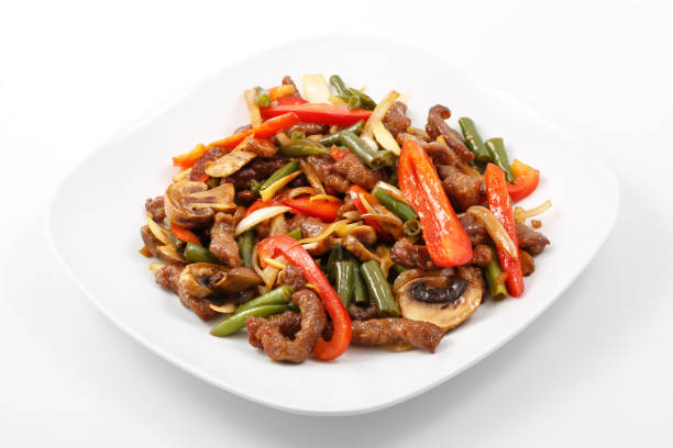 meat in Chinese, pork, Chinese sauce, mushrooms, green beans, bell pepper meat in Chinese, pork, Chinese sauce, mushrooms, green beans, bell pepper in white plate on  white background mongolian culture stock pictures, royalty-free photos & images