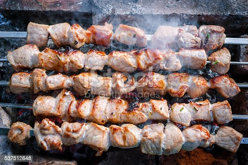 Pieces of grilled meat cooked on the grill over the coals