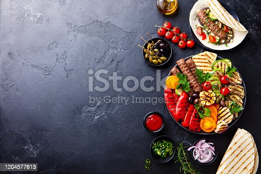 655793486 istock photo Meat kebab, vegetables on a black plate with tortillas, flat bread. Slate stone background. Copy space. Top view. 1204577613
