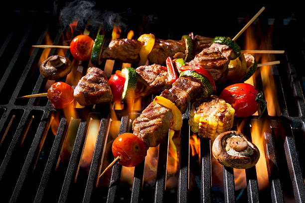 Meat kebabs with vegetables on flaming grill Barbecue skewers meat kebabs with vegetables on flaming grill spit roasted stock pictures, royalty-free photos & images