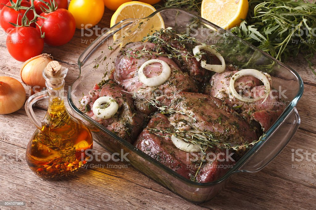 Meat marinated with onions, herbs and lemon close up. horizontal stock photo