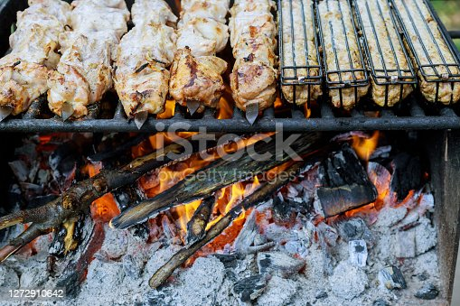 Meat on metal skewers is grilled with burning charcoal.