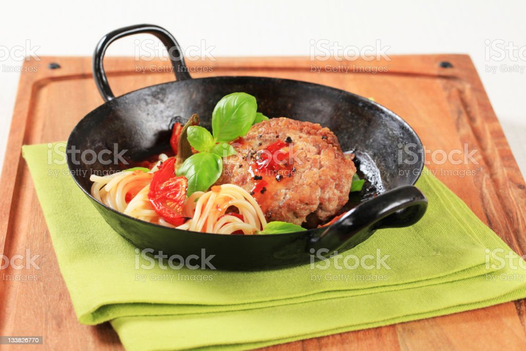 Meat patty with tomatoes and spaghetti royalty-free stock photo