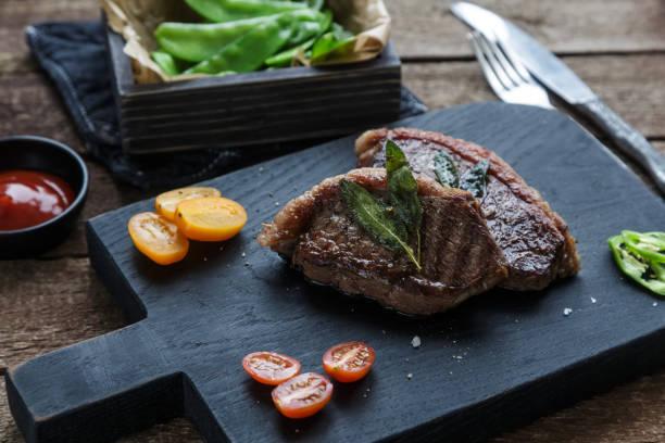 Meat Picanha steak, traditional Brazilian cut on black cutting board. stock photo