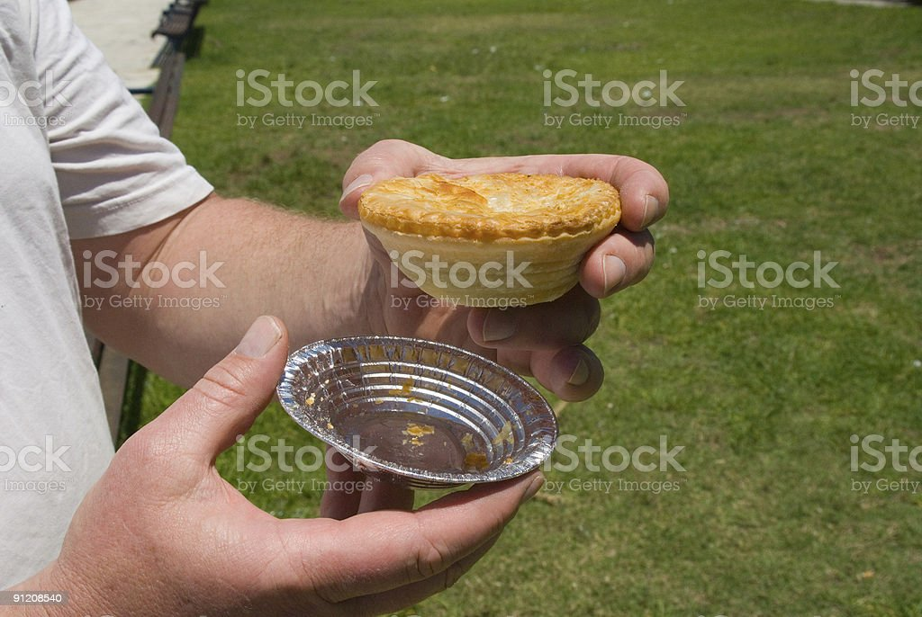 Meat Pie from Australia in mens hand with foil stock photo