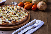 istock Meat pizza on wooden board. Made with Mozzarella, picanha meat, onion, cheese, tomato sauce. Filet Steak, meat, fork and knife. Horizontal photo with raw ingredients. 1240627199