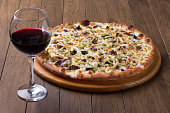 istock Meat pizza on wooden board. Made with Mozzarella, picanha meat, onion, cheese, tomato sauce. Filet Steak, meat. Glass of red wine to accompany. Gastronomic Photo. 1240627202
