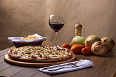 istock Meat pizza on wooden board. Made with Mozzarella, picanha meat, onion, cheese, tomato sauce. Filet Steak, meat, pepper grinder, glass of red wine, crostini, fork and knife. Horizontal Photography. 1240627204