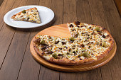 istock Meat pizza on wooden board. Made with Mozzarella, picanha meat, onion, cheese, tomato sauce and olives. Filet Steak, meat. Served slice of pizza on a white plate and sliced pizza on the side. 1240628249