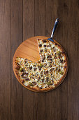istock Meat pizza on wooden board. Made with Mozzarella, picanha meat, onion, cheese, tomato sauce and olives. Filet Steak, meat. Pizza without a slice. Top photo with spatula. 1240628255