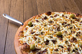 istock Meat pizza on wooden board. Made with Mozzarella, picanha meat, onion, cheese, tomato sauce and olives. Filet Steak, meat. Ready to serve. 1240628506